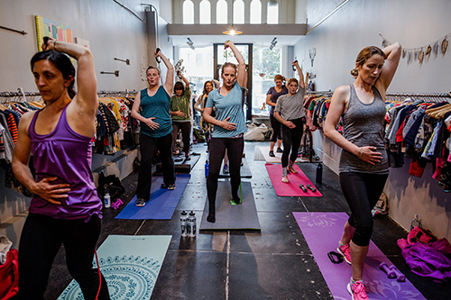Pregnant women exercising on yoga mats.
