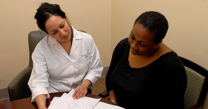 Doctor looks over paperwork with patient.