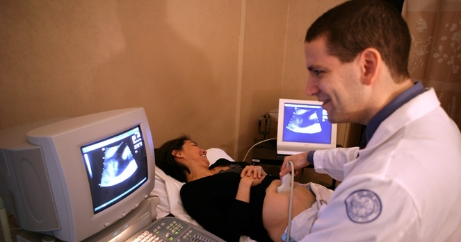 Doctor performs ultrasound on patient.